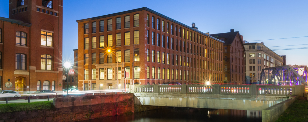 Photograph taken at twilight of two façades of a five-story brick mill building flanked by two large mill buildings beside a canal.