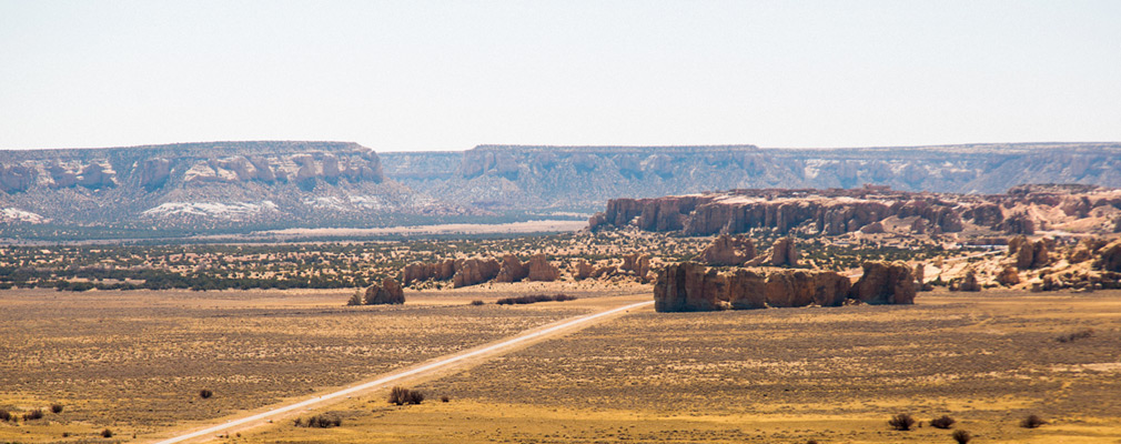 Panoramic photograph of the landscape of the Acoma Pueblo, with Sky City on the top of the mesa in the middle ground.