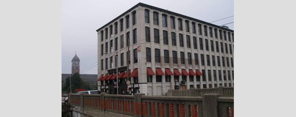 Photograph of two façades of a five-story brick building painted gray, with a canal bridge in the foreground and the tower of an adjacent mill building in the background.