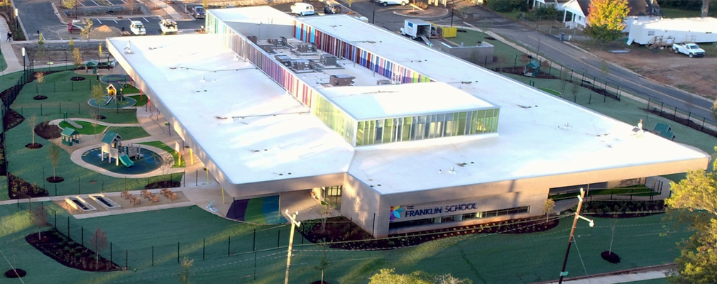 Low-angle aerial photograph of a one-story school building, with play equipment next to the building.
