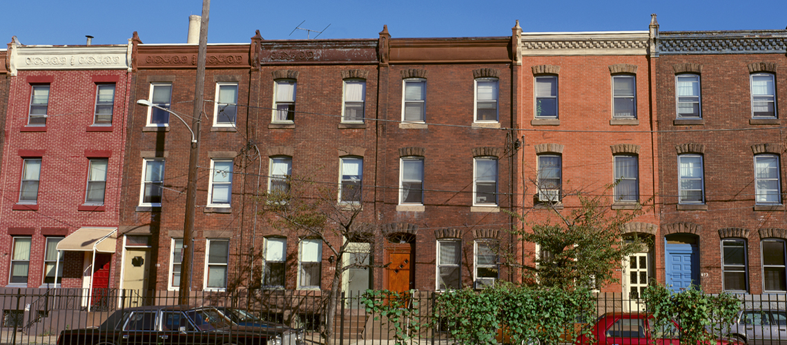 Image of three-story brick rowhouses on a city block.