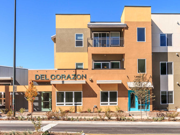 "Image of a three-story apartment building taken from ground level, with the name ""Del Corazon"" over the entrance."