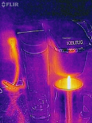 A Thermal image of a coffee machine pouring coffee into a mug, in which the heat flowing through the electrical cord and the coffee are visible.