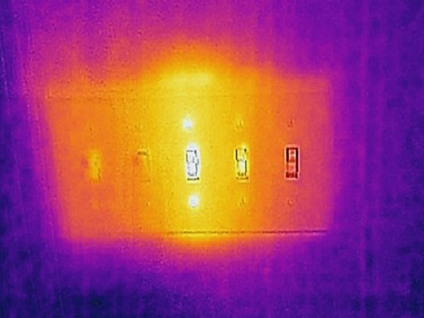 Thermal image of a light switch in operation and with visible electricity.