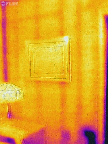 Thermal image of a wall, in which the studs and exterior outlet are visible, as is heat loss in the corner. The table lamp and picture frame on the wall are also visible.
