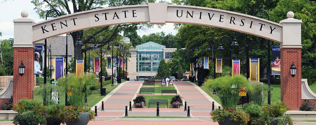 "Photograph of an archway with the words ""Kent State University"" at the start of the esplanade, with two wide walkways; benches and lights; and lawns, bushes, and mature trees. A multistory university building ends the vista down the esplanade."