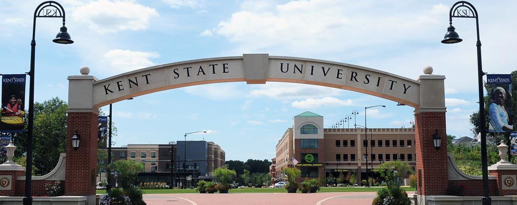 "Photograph of an archway with the words ""Kent State University,"" with new multistory buildings in the background."