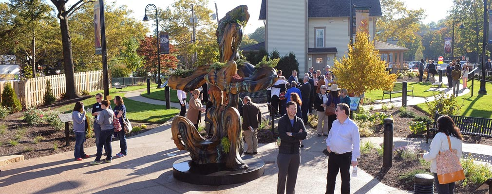Photograph of groups of people talking near a sculpture behind a three-story residential building.