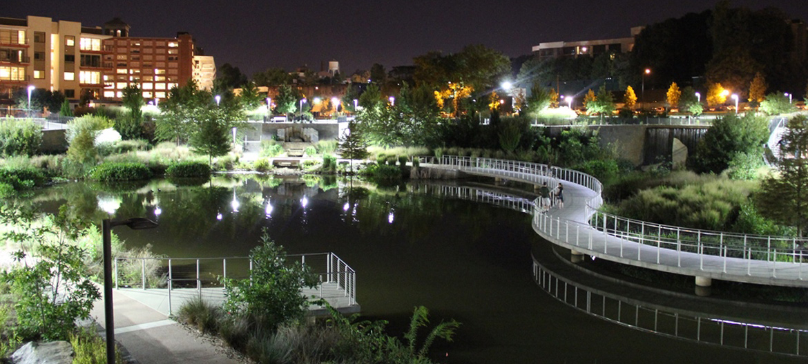 The photograph shows a picture of the park in the evening; a walking trail follows a water feature and greenspaces are lit during the evening.