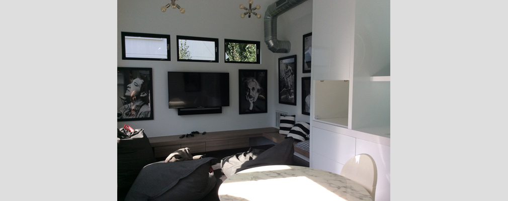 An interior view of an accessory unit showing a sitting area with a television and framed pictures on one wall.