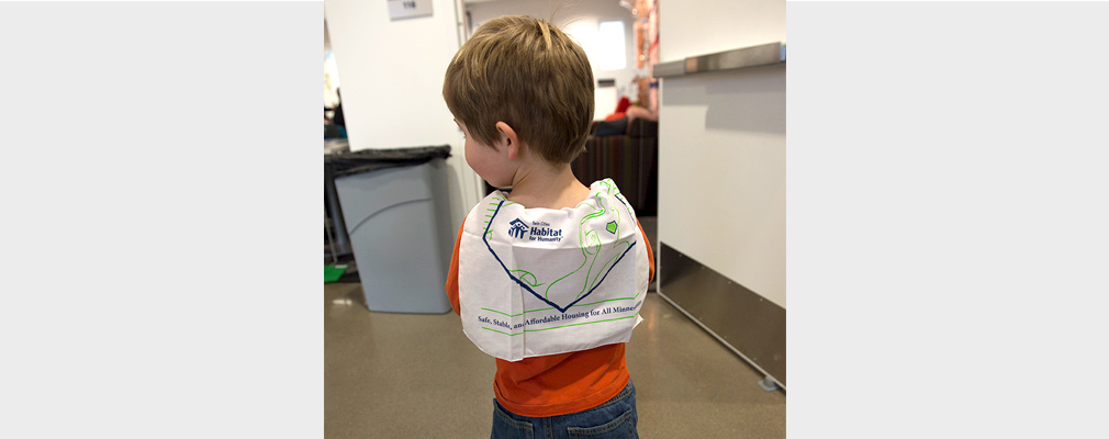 A little boy is seen from behind with a Habitat for Humanity cloth poster wrapped around his shoulders.