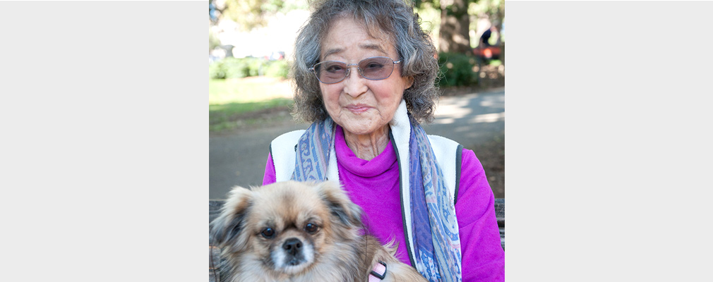 An older woman poses for the camera holding her dog.
