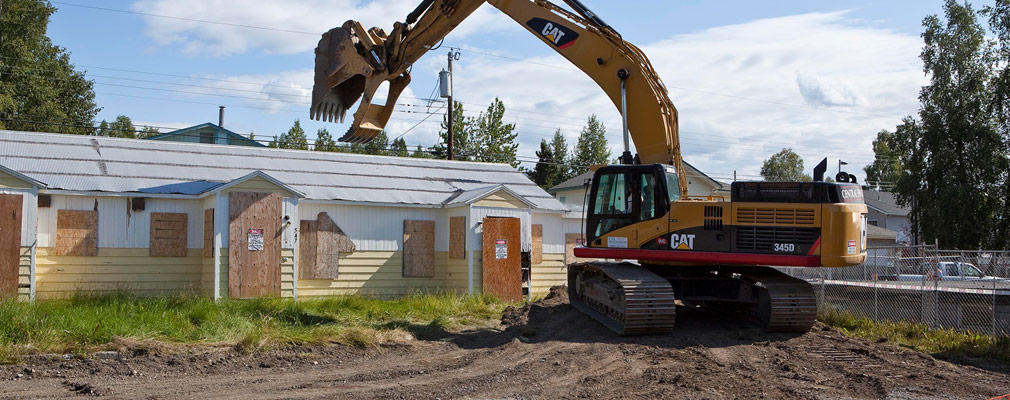 Photograph of a boarded-up home in the process of being demolished with heavy machinery.