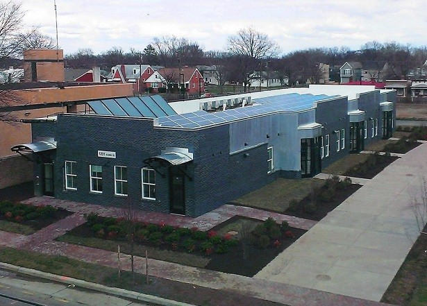 A photograph taken approximately 30-feet above street level showing the front and side façades and the solar panels on the roof of the seven unit senior building, a brick, one-story structure (courtesy of Better Housing Coalition).