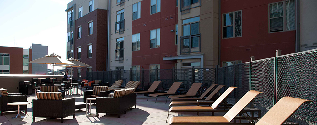 Photograph of a terrace behind one of the U Square @ the Loop buildings furnished with reclining pool chairs and arm chairs arranged around tables.