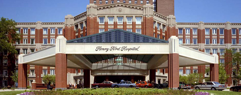 A photograph of the front façade of the Henry Ford Hospital building, a brick building six stories tall. The entrance is highlighted with a large three-sided extension, with a shallow pediment over the front side of the bay.  In front of the entrance bay is a large octagonal port cochere that has a glass pedimented roof over its center; approximately six cars are parked under the port cochere. 'Henry Ford Hospital' is written in script on the frieze of the porte cochere.