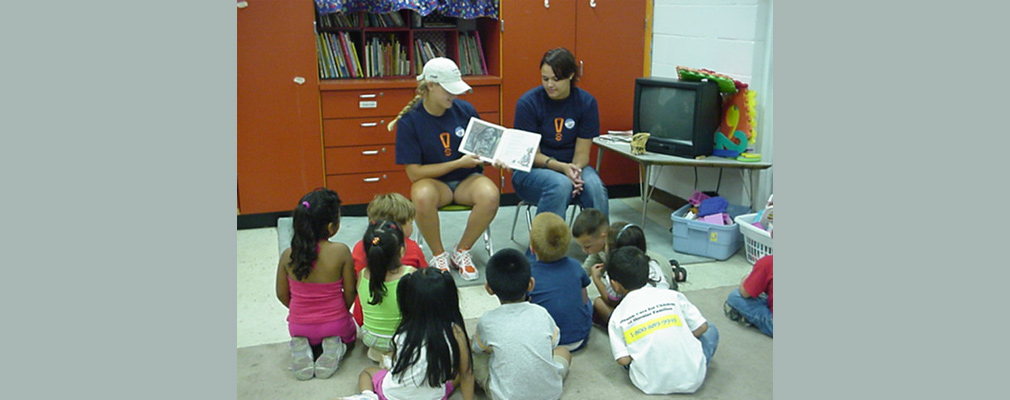 Photograph of two IUPUI students reading to young children.