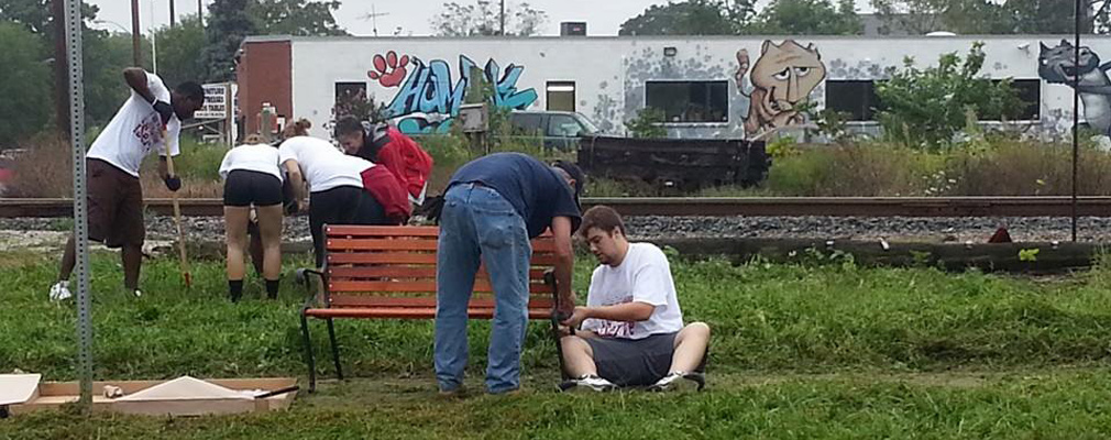 Photograph of IUPUI student volunteers cleaning a neighborhood park and installing a park bench.
