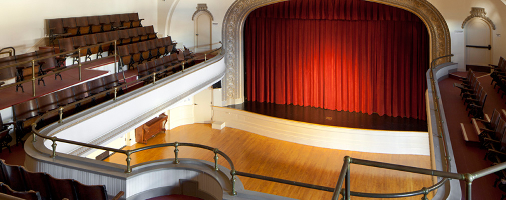 Photograph taken from the balcony showing the proscenium stage and wood floor of the auditorium.