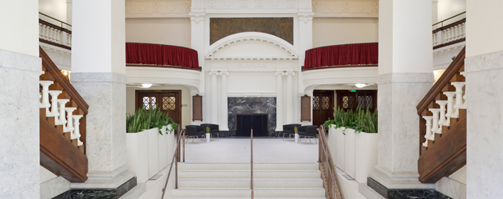 Photograph of the top of the grand staircase with the lobby in the background.