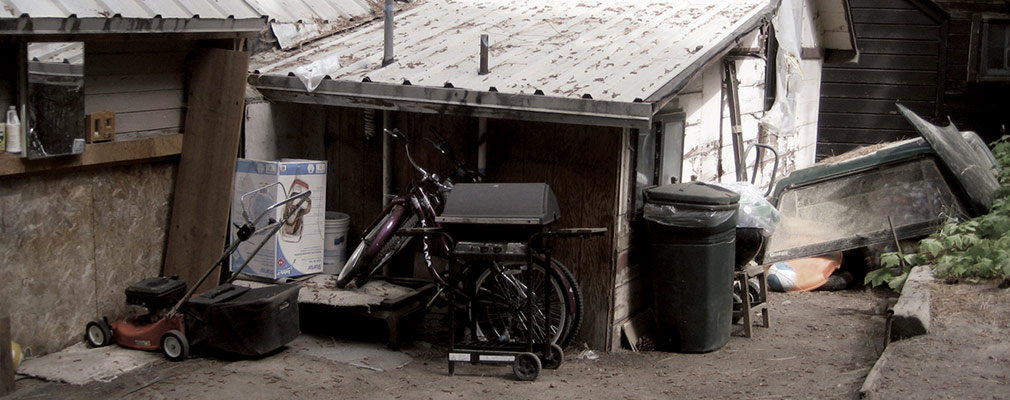 Photograph taken from street level of a one-story wooden house with a metal roof. A lawnmower, grill, trashcan, and two bicycles, are scattered near the entrance to the house. Elsewhere on the lot are a trashcan and an overturned wooden boat.