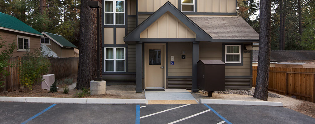 Photograph of the front façade of a two-story, front-gabled building with wood siding. The front door is accessible from the parking area in front of the house.