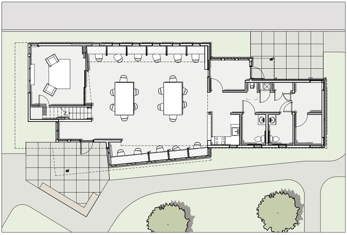 Floor plan of the community center showing the building entrance, a partially enclosed room and the stairway to the loft on the left side of the building. The center portion of the building is one large area accommodating 10 desk carrels along the outside walls and two 6-seated tables in the middle of the room. The right side of the building contains ancillary rooms, including a staff office, a small kitchen, and restrooms.