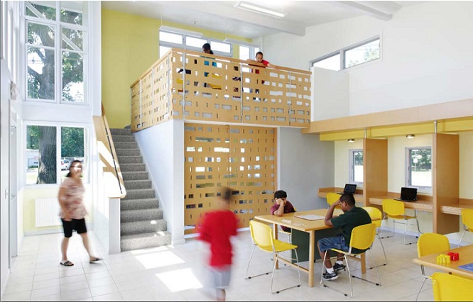 A photograph of the inside of the center's large room. An adult is walking inside the building entrance. A child walks in the central portion of the room, where two other children are studying at one of tables. Three desk carrels line the side wall. Behind the children are a small room and stairs leading to the loft, occupied by four children.