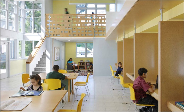 A photograph of the central area taken from the staff office. Two children sit at two tables and two other children occupy two of the five desk carrels on the right side of the photo graph. In the background are the building entrance, stairway to the loft, the loft (where two children are standing), and the reading room (underneath the loft, where a child is seated).