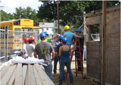 A photograph of nine instructors and students, all wearing hardhats, in the construction zone, with lumber in the foreground and a partially constructed wall near the students. A school bus is in the middleground behind a chain-link fence.