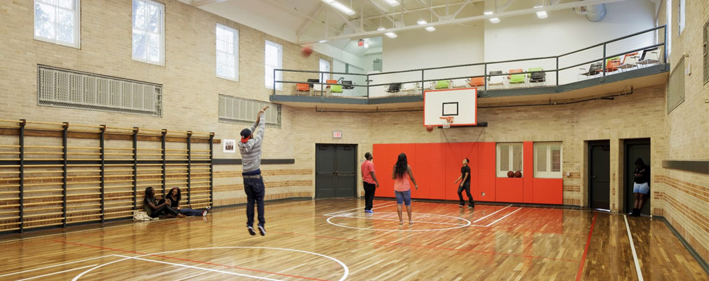 Photgraph showing young adults and children playing on an indoor basketball court.