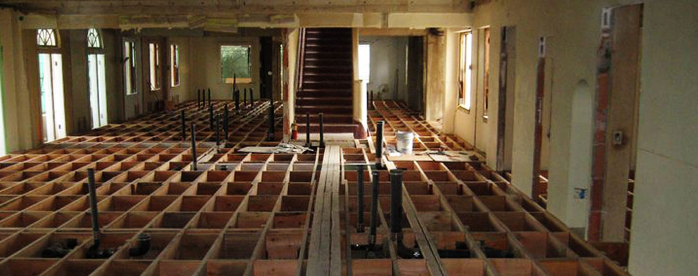 Photograph of a room with exposed floor joists and pipes.