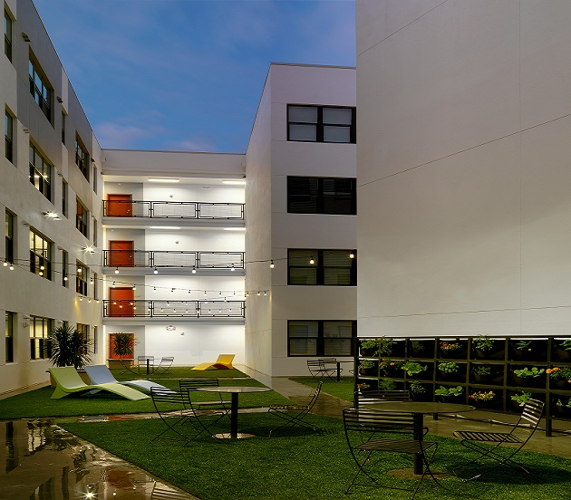 An evening photograph of the courtyard framed by the four residential stories of the apartment building. The courtyard is grassed, with concrete sidewalks. Three lounge chairs and four bistro tables with chairs stand in the grassed areas. Strings of lights are hung overhead.