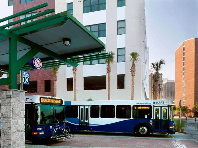A photograph taken at street level of two buses in the Marion Transit Center, with the Metro 510 apartment building in the background.