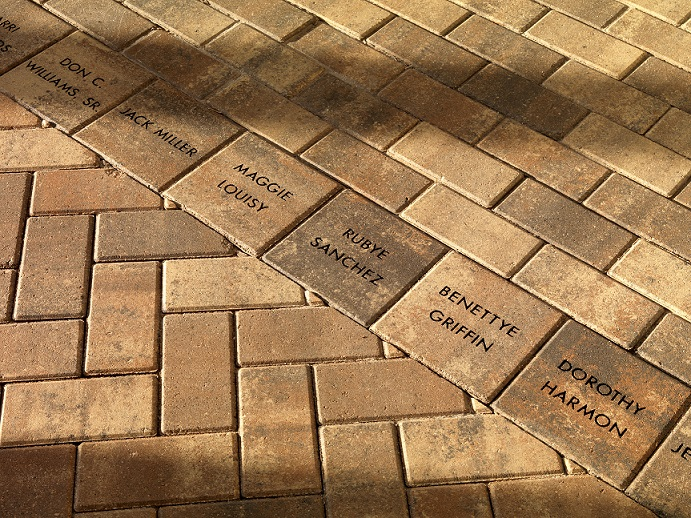 A picture of a portion of the memorial brick walkway. Eight of the bricks are stamped with the names of congregation members.