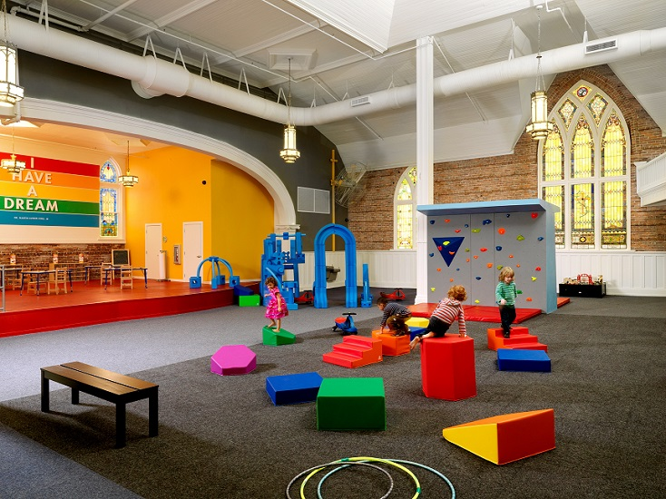 A photograph of the play space inside the church. Four preschoolers play on brightly colored geometric forms in the middle ground. Other play equipment stands behind the children. A bench and several hoola-hoops are on the floor in the foreground. To the rear, the play area is framed by a stage and an exterior wall of the church, with exposed brick and two stained glass windows.