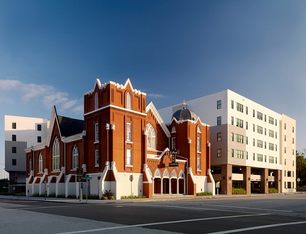 Photograph taken at street level of the Metro 510 development on the opposite corner of an intersection. The photograph shows the front and side facades of the St. James A.M.E. Church, a brick neoGothic building at the corner. To the side and rear of the church is the apartment building, with four residential floors above a two-story parking garage; the facades of the apartment building are very plain, with no ornamentation, serving as a backdrop to the historic church.