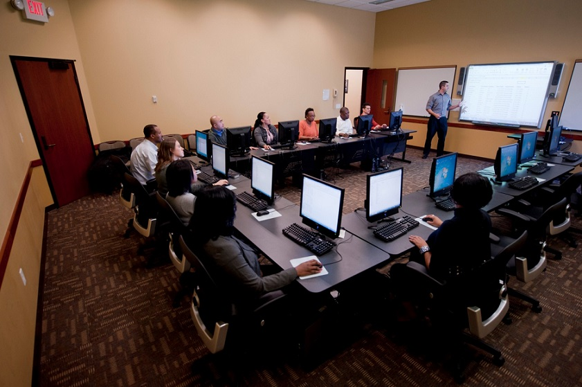 Photograph taken from an elevated position of a computer room, with 14 computers and 10 students at a U-shaped table. At the open end of the table, an instructor is pointing to an enlarged projection of the computer screen.