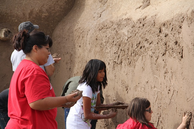 A photograph of six women, men, and children mud plastering an adobe home (courtesy of Tanya Hammiddi).
