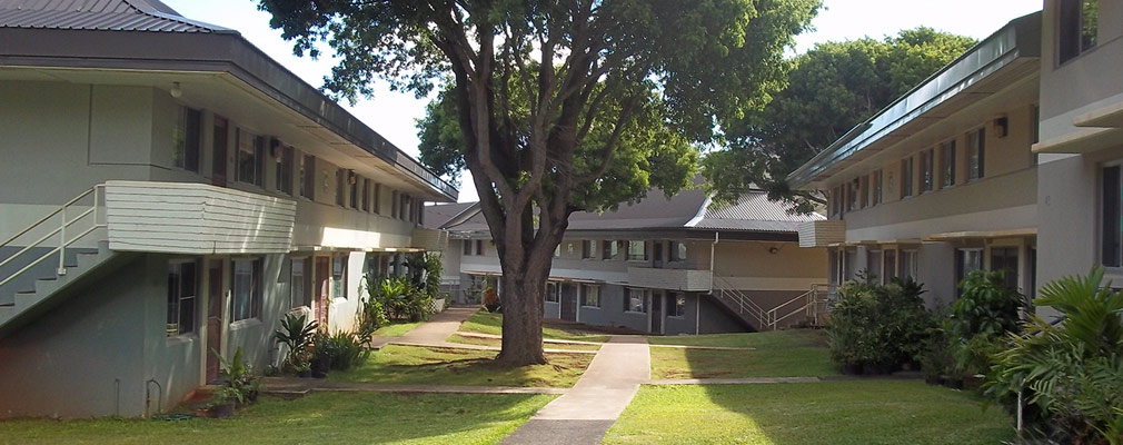 Photograph of three two-story residential buildings with a connecting lawn and concrete walkway.