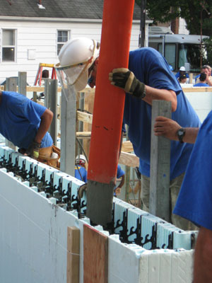 A worker filling an ICF wall with concrete.
