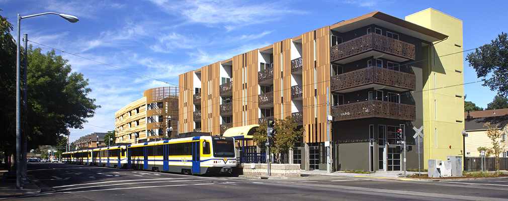 Photograph showing a light rail train stopped in front of four-story apartment buildings.