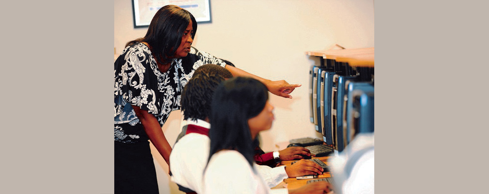 Photograph of an instructor and people using computers at the Technology Center.