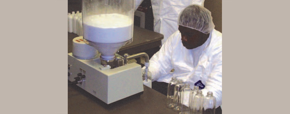 Photograph of a Sweet Beginnings employee using processing equipment.