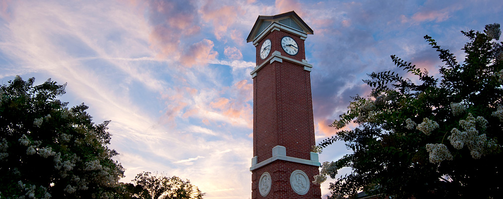 Photograph taken from ground level looking up at the Winston-Salem State University clock tower at dusk. The tower is made of brick highlighted with light-colored stone, and two of its clock faces are shown. Trees are planted around the tower.