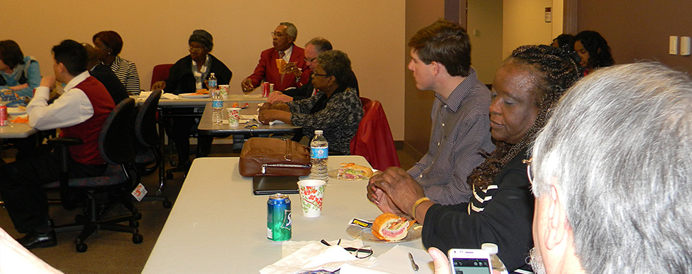 Photograph of approximately a dozen people seated at tables looking toward the front of the room. On the tables are sandwiches, sodas, and water bottles.
