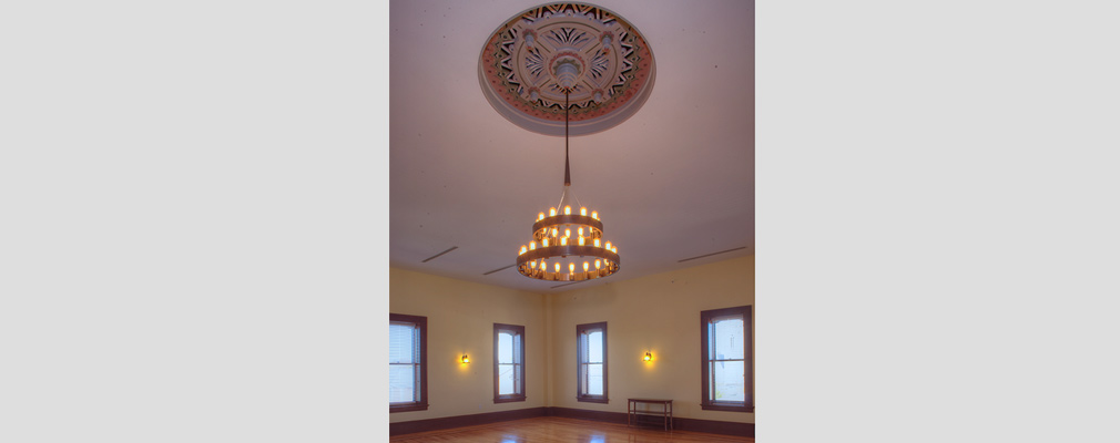 Photograph of a two-tiered chandelier descending from a ceiling medallion in a large room.