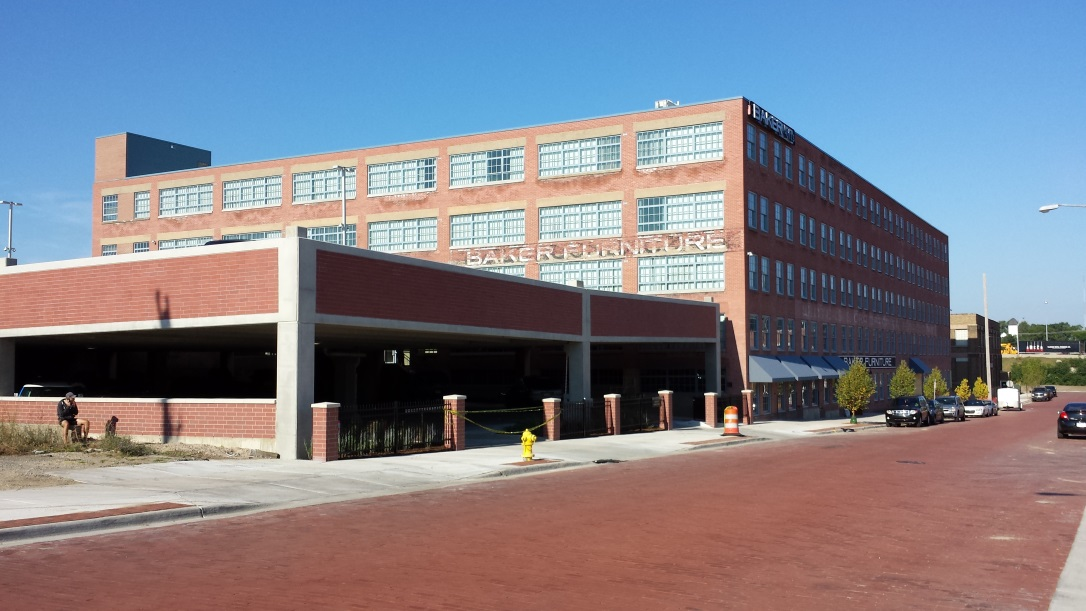 "Photograph taken at street level from across the street showing two facades of a five-story brick building with a flat roof. ""Baker Furniture"" in faded paint is written above the third-story windows on one of the facades. In the foreground, a two-level brick-faced parking structure stands beside the converted industrial building."