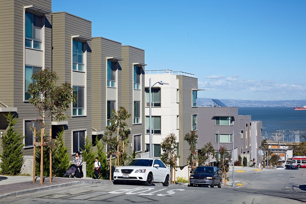Photograph depicting multi-story residential buildings and the adjacent streetscape, including cars parked along the road and pedestrians traveling along the sidewalk. Views of the San Francisco Bay are visible in the background.