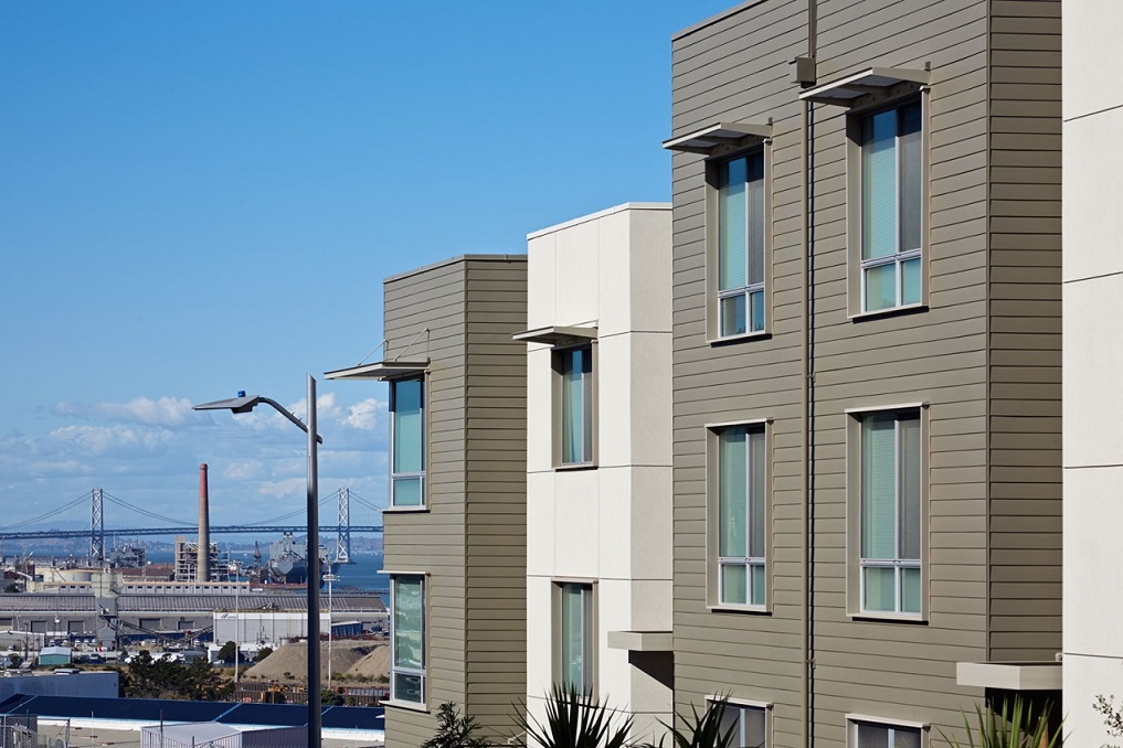 Exterior image displaying the upper floors of a multi-story residential building, with a view of the San Francisco bay in the background.
